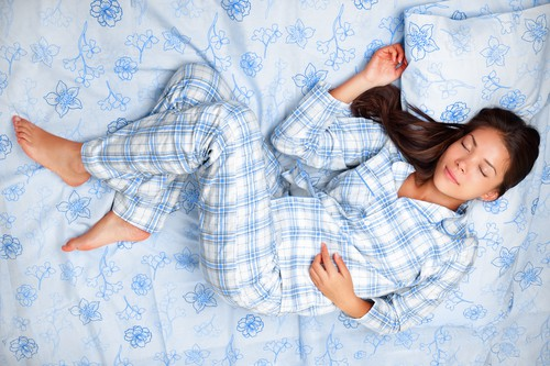 comfy clothes women love - woman in bed in pajamas