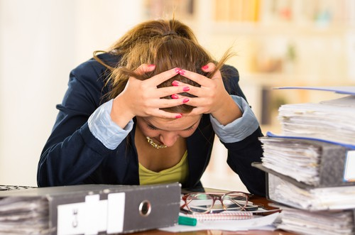 what is adrenal health - stressed out woman surrounded by work files